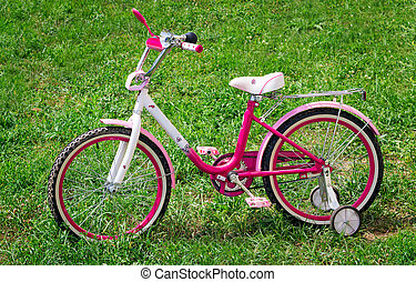 The bicycle for the girl on a green lawn.