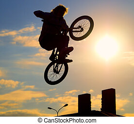 bicyclist - The bicyclist on a bicycle in a jump, on a ...