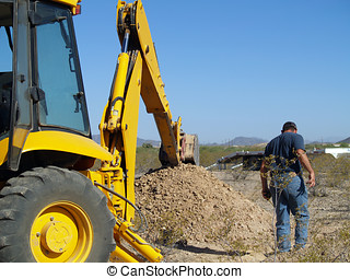 The Big Dig - A construction worker inspecting a hole he had...