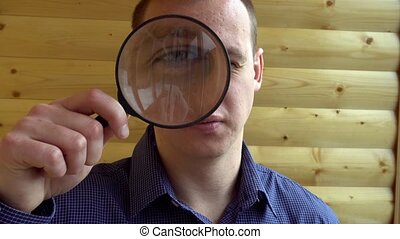 The big face of a curious man looking at the camera with a magnifying lens a detective private eye