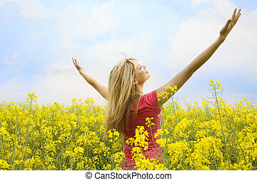 happy blond girl with open arms in a big hug to the sky in a yellow field