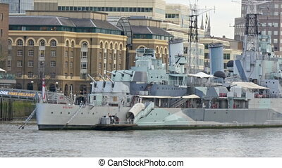The big warship on dock on Thames river. The white warship...