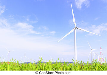 The big windmill turbine field with the grass foreground and the blue sky
