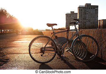 The bike stands on a special parking in the background of the setting sun. Sunset in the city.