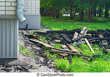 The Black Charred Rafters, Roof Framework, Nails Sticking Out, Debris on the Lawn near the Apartment Building with Downspout After the Fire. Insurance Concept.