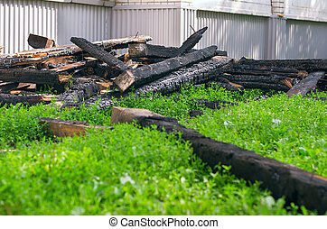 The Black Charred Rafters, Roof Framework, Nails Sticking Out Dumped on the Lawn near the Apartment Building After the Fire. Insurance Concept.