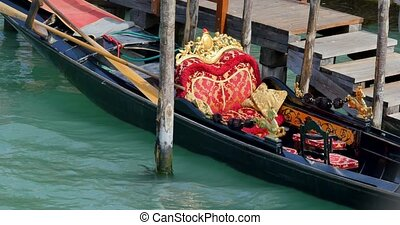 The black gondola is floating on the water.