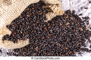 The black rice and a bag of burlap on old wooden background