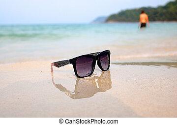 sunglasses on the beach near the sea water