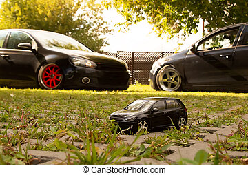 The black toy car stands on the background of two such real cars.