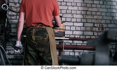The blacksmith works with the furnace, slider