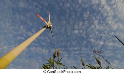 The blades of the wind station are spinning against the...