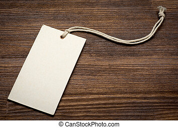 the blank price tag label on wooden background close up