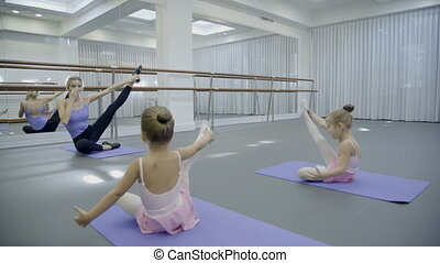 The blond ballet teacher leads the stratching with her two...