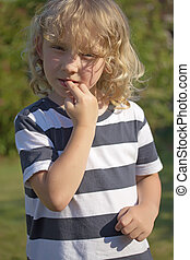 The blond boy in a striped shirt is biting his nails. Vertically.
