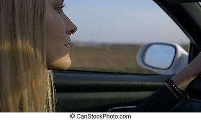 The blonde at the wheel of a car