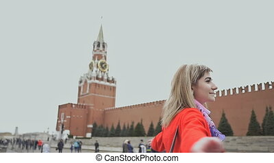 The blonde girl is happy to be in Moscow. The girl is pleased with the panorama and beauty of the Kremlin towers on Red Square