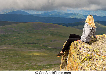 The blonde girl sits dangerously alone on the edge of the cliff above the abyss in the mountains of Altai, hanging her legs down over the lake and looking out into the clouds on the peaks of the hills