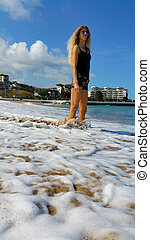 the blonde girl stands in the foam of the surf