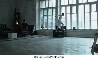 The blonde in a white dress jumps on an armchair, and from an armchair on a window sill. Sexy young woman dances on against a large window.