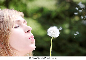 The blonde in park with a dandelion in hands