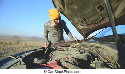 The blonde in the cap looks under the hood of the car is...