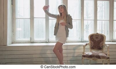 The blonde on the opposite window makes a selfie in a white room made of wood. A beautiful young woman in a short dress takes pictures of herself through the phone with a flash.