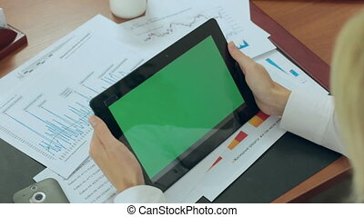 The blonde works in an office with the tablet with a green screen