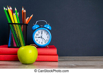 The blue alarm clock along with multi-colored pencils stand on a stack of red books, next to an apple