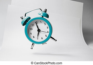 The blue alarm clock bounces against the background of business papers.