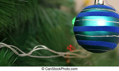 The blue ball is swinging on a Christmas tree.