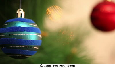 The blue ball is swinging on a Christmas tree