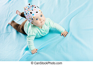 baby in hat crawling on the blue coverlet