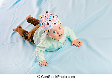 blue-eyed baby in hat crawling