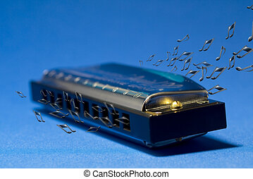 A photo of a harmonica and notes, on a blue background.