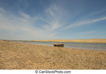 The boat in the water. Rowing boats in the reeds. Wooden boat on the lake on a summer day. Aral sea, Kazakhstan
