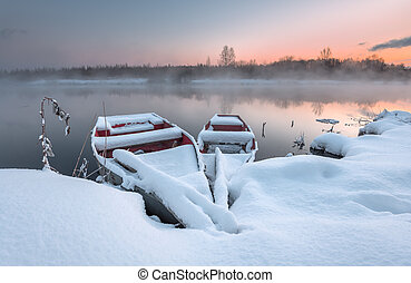 The boat in the winter on the freezing lake