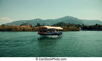 the boat sails between the mountains on the river