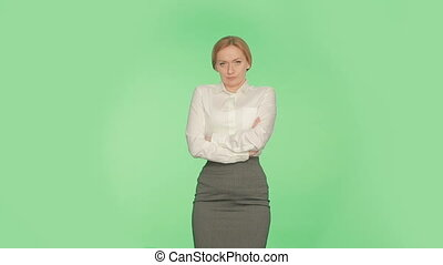 the body language of a woman on a green background. arms. Chroma. uncertainty.