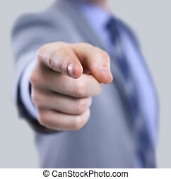 The body of a business man in a suit pointing with his finger