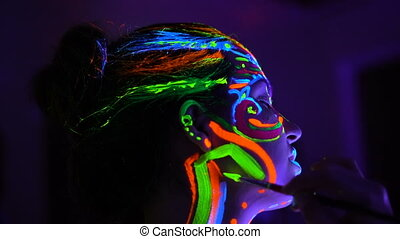 The bodyart ultraviolet painter draws on the face of...