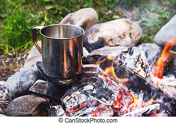 The boiling liquid in a stainless mug stands on stones with coals in a fire