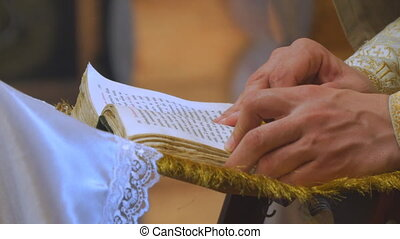 The book is in the hands of a priest
