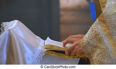 The book is in the hands of a priest or clergyman