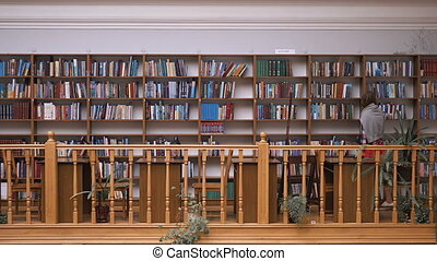 The Bookshelves Wall in Library - Young casual student girl...
