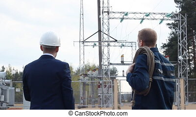 The boss hands over the commands to the worker against the background of the power plant
