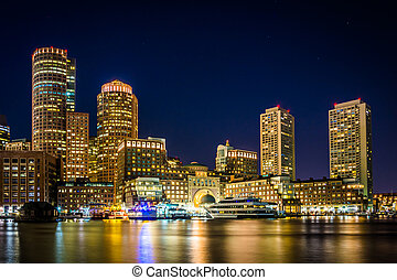 The Boston skyline and Rowes Wharf at night, seen from Fort Poin