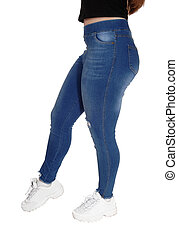 The bottom and legs of a young girl in jeans