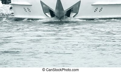 The bow of a moving motor yacht and water surface - The bow...