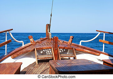 The bow of old wood ship in blue waters of Mediterranean sea